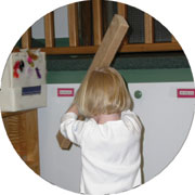 Young child hitting the wall with a board.