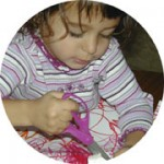 Young girl using scissors.