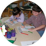 Two children sitting at a table drawing pictures.