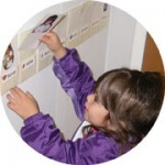 Young child putting her name card on chore chart.