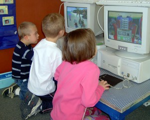 Three children using computers.