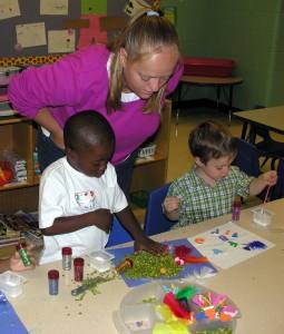 Teachers watching children during an art project.