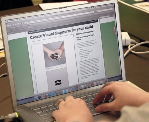 Student reviewing a visual support's paper on a laptop.