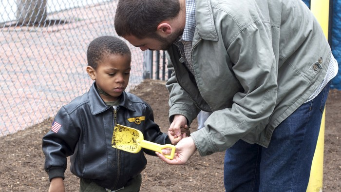Teacher speaking with student on the playground.