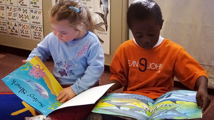 Two Pre-K children looking at books.