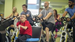 A man with a disability is working out at the gym on a cycling machine.