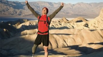 Hiker with an artifical leg reaches the top of a mountain.
