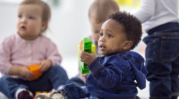 A multi-ethnic group of toddlers sitting on the floor playing with plastic blocks.