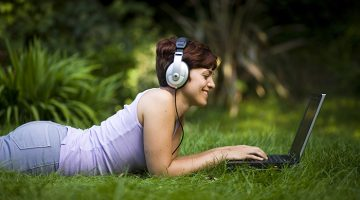 Young female student using laptop and headphones whilst lying on the grass.
