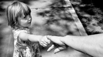 Young girl reaching for an adult's hand.