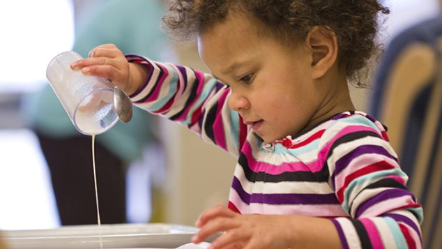 Little boy pouring milk into a bowl.