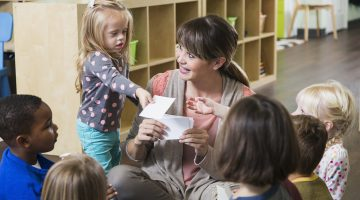 A preschool teacher sitting on the floor with a group of multi-ethnic children in a circle. They are watching her as she holds up a card. A little girl, a special needs child with down syndrome, is standing beside her handing a card to another child.