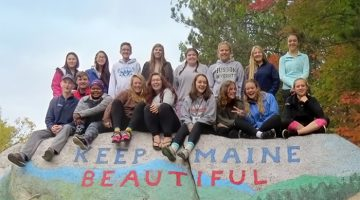 Group of teens sitting on top of large granite boulder with the words, Keep Maine Beautiful painted on it.