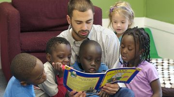 Pre-K teachers reading to his students.