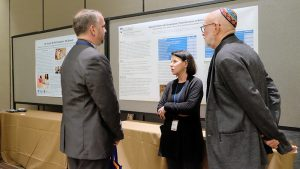 Conference attendee talking with Liz DePoy and Stephen Gilson about their poster.