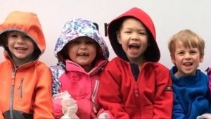 Four preschoolers smiling wearing their coats with hoods.
