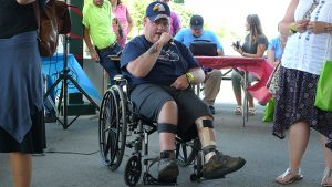 Disability Pride 2019 featured speaker, a man seated in a wheelchair addressing a crowd.