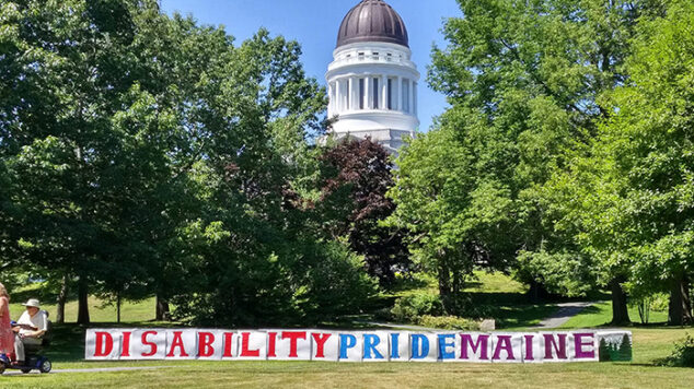 Maine Capitol in background with Disability Pride Maine banner along the park.