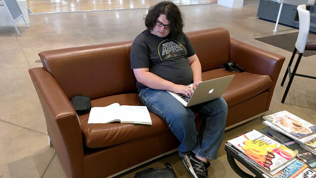 Student seated on a couch studying.