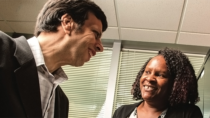 A man mentoring a woman employee.