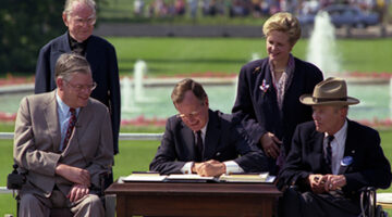 President George H. W. Bush signing the Americans with Disabilities Act of 1990 into law on the South Lawn of the White House (07/26/1990).