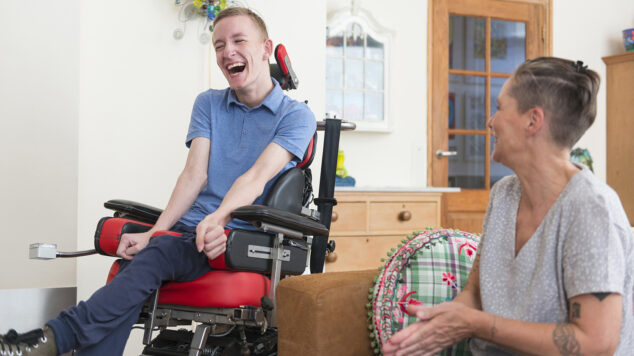 Young adult man in a wheelchair and woman sitting on a couch.