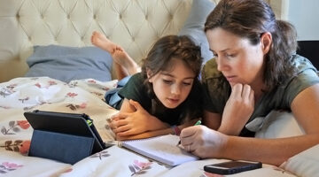 School-aged daughter and her mother doing homework together in a bedroom.
