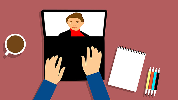 Clip art of person typing on a laptop.