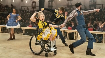 Actor Ali Stroker in a wheelchair pumping her fist with other actors dancing around her during Broadway revival of Oklahoma!