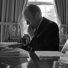 President Gerald Ford sitting at the desk reviewing paperwork in 1975.