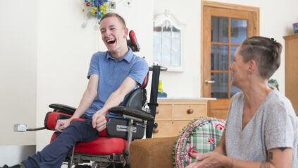 Young Adult man in a wheelchair in his living room with his mother.
