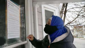 Hibo Omer standing outside a house on Maple Street in Lewiston, Maine, reading an official notice of environmental lead hazards taped to the front door.