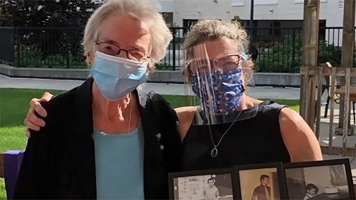 Two masked older women standing side-by-side outside. The woman on the right has her right hand on the other woman's shoulder and is holding a collage of framed family photos in her left hand.