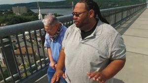 An African-American man and a senior white man with developmental disabilities walking along a pedestrian walkway overlooking a river.