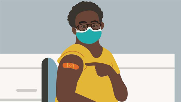 Young woman of color seated, wearing a blue face mask, pointing to a Band-Aid on her right arm after receiving the COVID-19 shot.