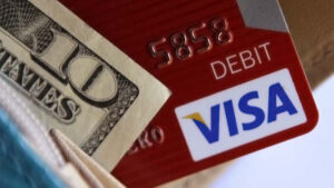 The corners of a U.S. ten-dollar bill and a red VISA debit card sticking out of a blue wallet.